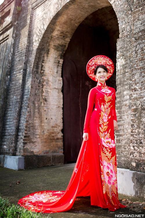 Áo dài đỏ với phần tà áo dài sau cách điệu cùng họa tiết dọc theo chính giữa thân áo khiến cô dâu trông thon gọn hơn