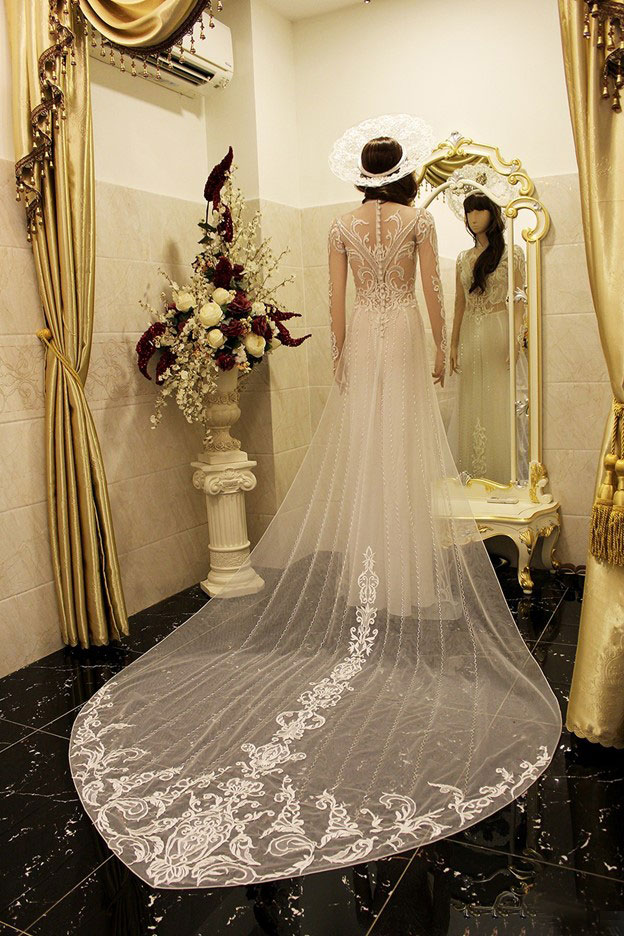 Kết hợp giữa ren hoa văn cùng tà áo cách điệu tạo cho bộ áo dài sự trang trọng trong ngày cưới