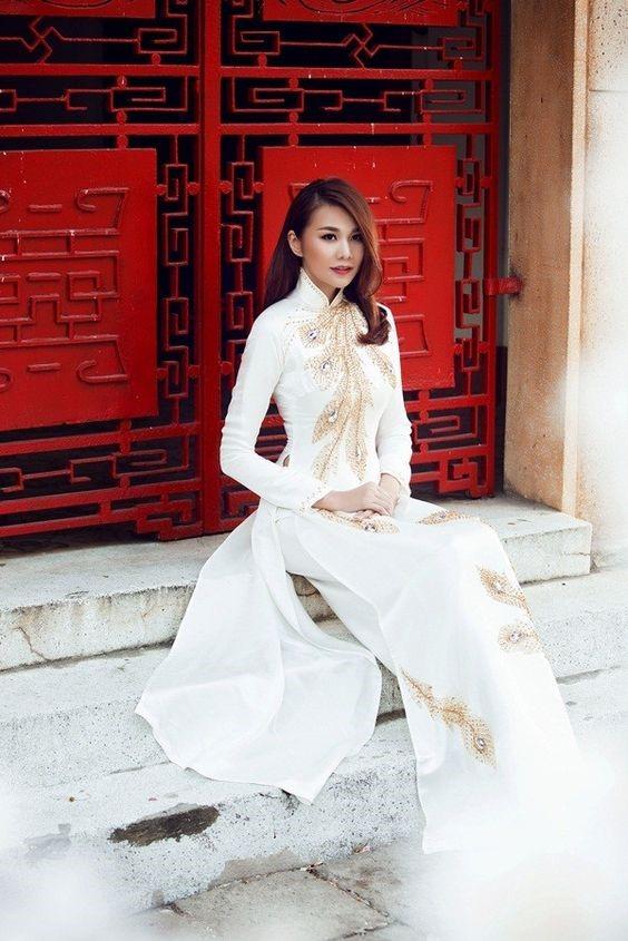 Mẫu áo dài trắng đính đá hình đuôi chim công đầy tinh tế với cổ áo cao duyên dáng